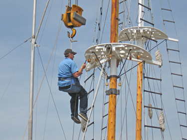man in harness working on rigging